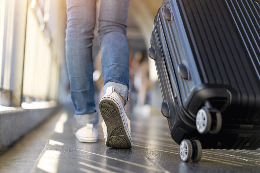 Femme voyageuse marchant seule avec sa valise. Voyage, week-end, vacances.