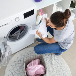 beautiful young woman doing laundry at home