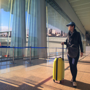 traveling woman and luggage walking in airport terminal and air